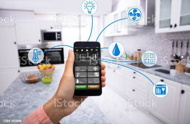 Woman's Hand Using Home Control System On Cellphone With Various Icons In The Kitchen
